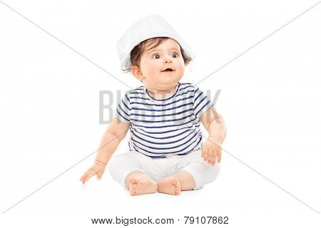 Cute baby girl in sailor outfit sitting on the floor isolated on white background