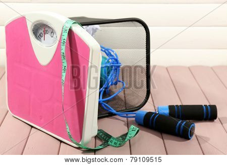 Metal trash bin with sport equipment, crumpled paper and weight scale on wooden floor and white wall background