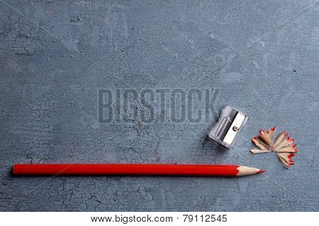 Pencil with sharpening shavings on texture wooden background