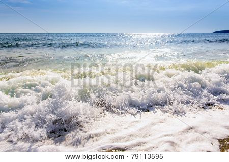 Sand Sea Beach And Blue Sky After Sunrise And Splash Of Seawater With Sea Foam And Waves