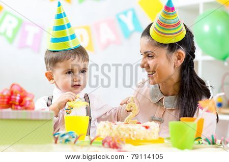Kid boy celebrating birthday holiday. Mom looking happily to her little son