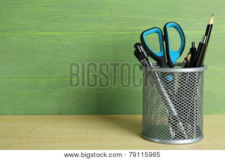 Metal holder with pens, pencil and scissor on wooden table and green wooden background