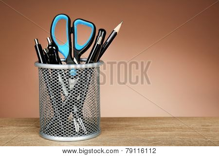 Metal holder with pens, pencil and scissor on wooden table and shaded color background