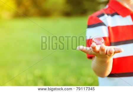Cute boy showing soap bubble in his open hand
