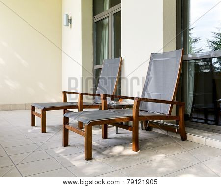 Two Chaise Longue On Balcony