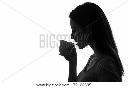 profile of woman holding and drinking cup of coffee or tea black and white isolated