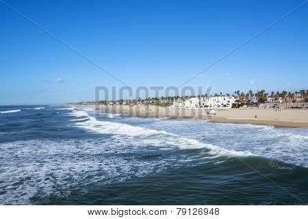 A panorama of the shoreline and sandy beach at historic Huntington Beach, California.