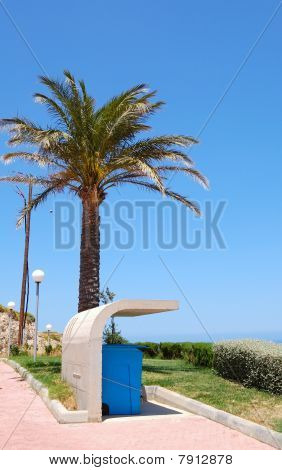 Garbage Bin Under Concrete Cover And Palm Tree, Crete, Greece