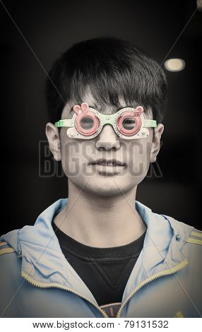 a chinese boy is wearing  special glasses in an ophthalmologist's office