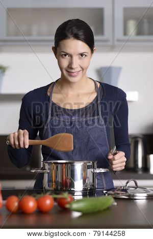 Happy Friendly Young Housewife Cooking Dinner