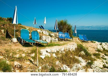 Sunbeds And Umbrellas (parasols) On A Rocky Beach In Corfu Island, Greece.