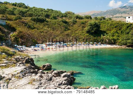 Kassiopi Beach, Corfu Island, Greece. Sunbeds And Parasols (sun Umbrella) On The Beach.
