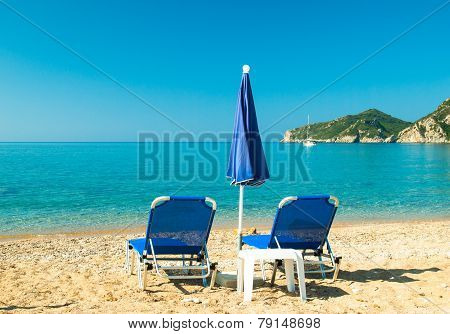 Blue Sunbeds And Blue Umbrella On A Beautiful Beach In Corfu Island, Greece