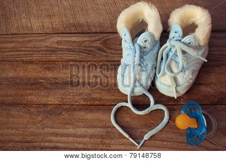 The heart symbol is drawn laces of children's shoes and a pacifier on the old wooden background. Ton