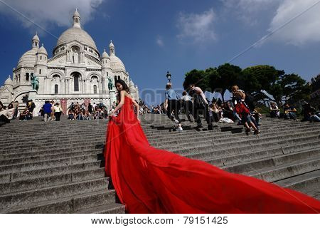 PARIS - SEP 10: model posing in red dress for photographer near Basilica of the Sacred Heart  on September 10, 2014 in Paris, France. Paris, aka City of Love, is a popular travel destination.