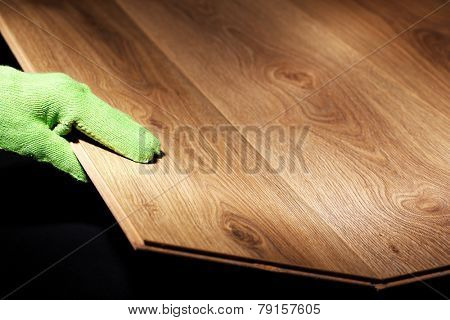 Carpenter worker installing laminate flooring