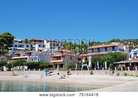ALONISSOS, GREECE - SEPTEMBER 23, 2012: People sit on the shingle beach at Rousoum on the Greek island of Alonissos. Rousoum was once the centre of the islands wine exporting trade.