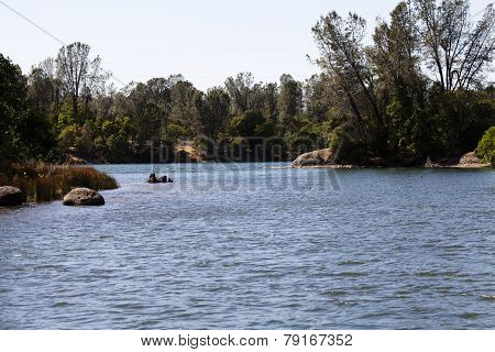 River Bend With Rocks And Trees On Shore