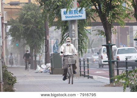 Cyclists cover their faces to protect from ash