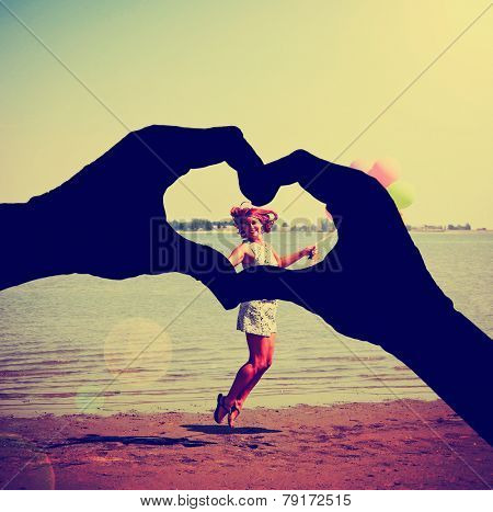 a silhouette of hands in the shape of a heart over a background toned with a retro vintage instagram filter effect