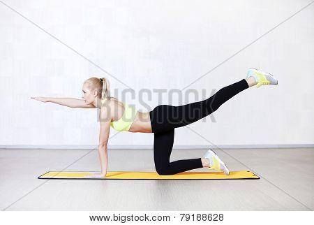 Young woman stretching before fitness exercises on a mat in a gym