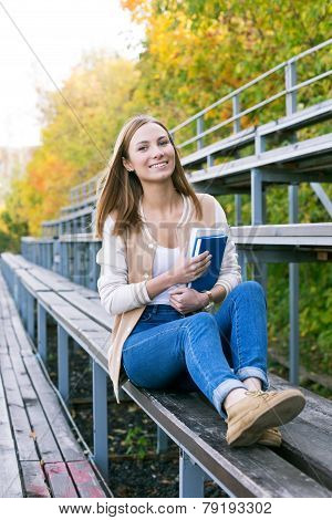 Student Sitting On Sport Tribune With Book And Smiling