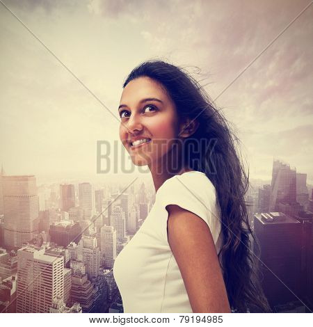 Smiling young Indian woman looking up into the sky against a misty modern cityscape with skyscrapers in a travel and vacation concept