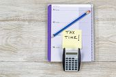 foto of reminder  - Horizontal top view of an office wooden desktop with small calendar calculator and sharpen blue pencil with reminder of doing Tax Returns - JPG