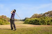 stock photo of cloud formation  - Male golf player teeing off golf ball from tee box wonderful cloud formation in background - JPG