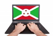 image of burundi  - Hands working on laptop showing on the screen the flag of Burundi - JPG