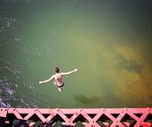 picture of trestle bridge  -  a boy jumping of an old train trestle bridge into a river   - JPG