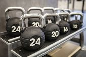 stock photo of kettlebell  - Heavy kettlebells weights in a workout gym - JPG