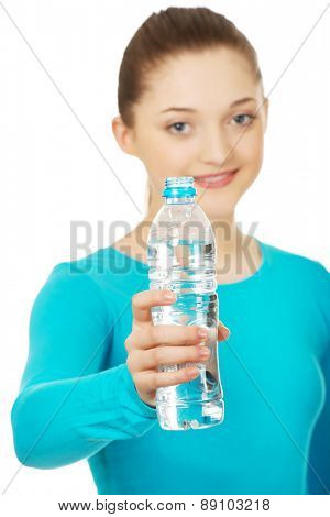 Beautiful teenage woman with bottle of mineral water.