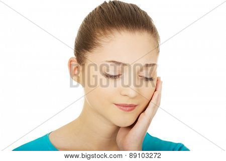 Teen woman with toothache touching her face.