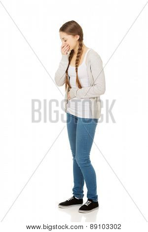 Sick teen woman about to vomit covering mouth.