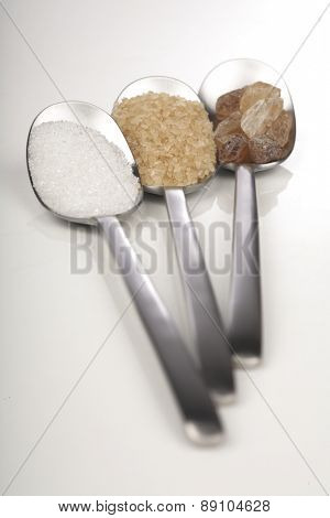 White and brown sugar on spoons
