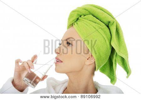 Beautiful woman in bathrobe drinks water.