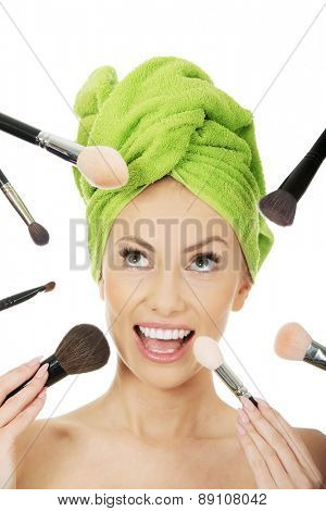 Beautiful shocked woman has brushes around face.