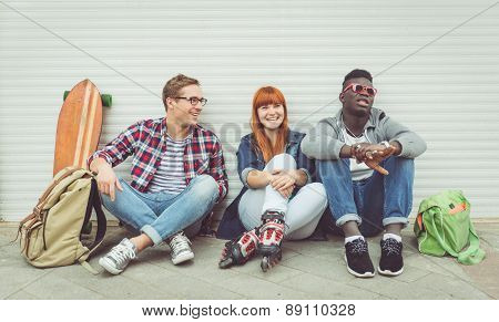 Three Mixed Race Friends Sitting And Having Fun