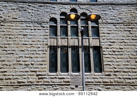 Lamppost in Front of the Stained Glass Windows of an Old Church
