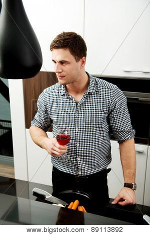 Man with his wineglass in the kitchen at home.