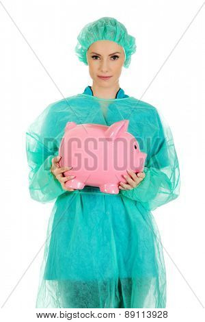 Female surgeon doctor with piggy bank.