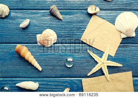 Card blanks with sea star and shells on wooden background
