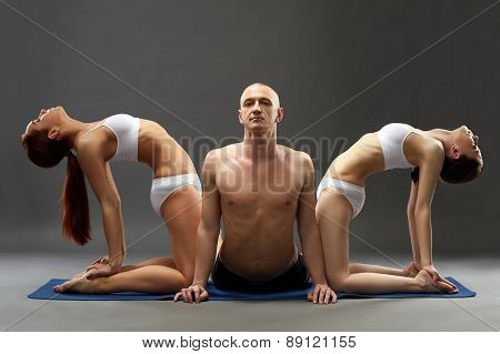 Relaxed people practicing yoga threesome in studio