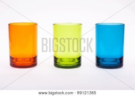 Modern color glass vases row on white reflective background