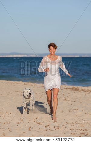 woman running on beach with pet dog