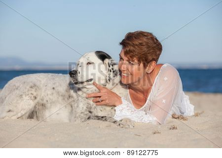 woman with old pet mongrel dog on beach