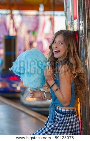 teen girl at carnival or fair with candy floss or cotton candy