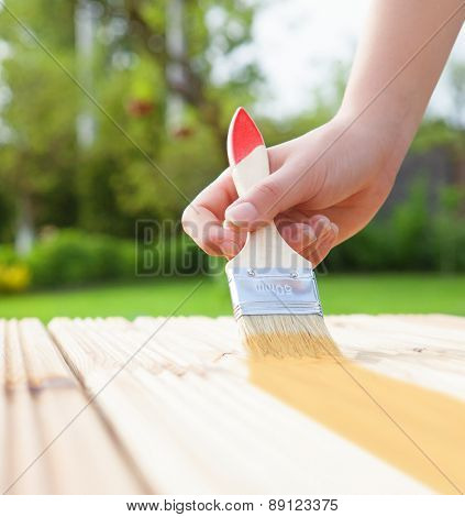 Applying protective varnish on a wooden furniture, diy house improvement concept