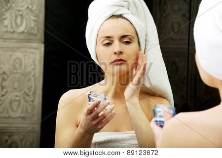 Attractive woman putting anti-aging cream on her face.